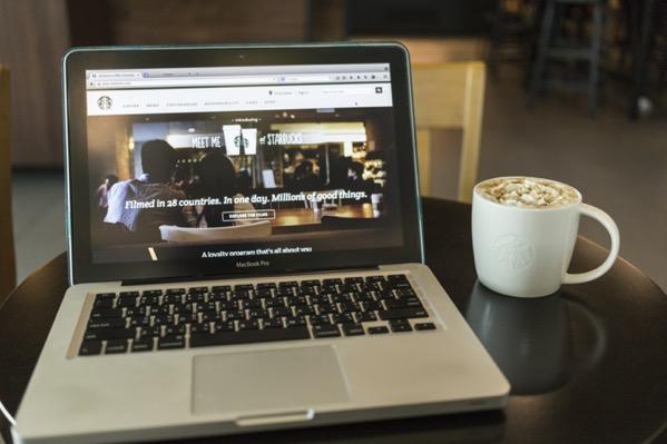 Chiang mai thailand october 02 2014 starbucks coffee caramel latte and apple laptop open starbucks website on monitor Sw51XJdhGl