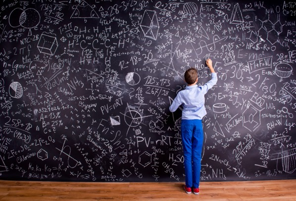 Graphicstock boy in blue t shirt writing with chalk on big blackboard with mathematical symbols and formulas rear view BdbAumHMb