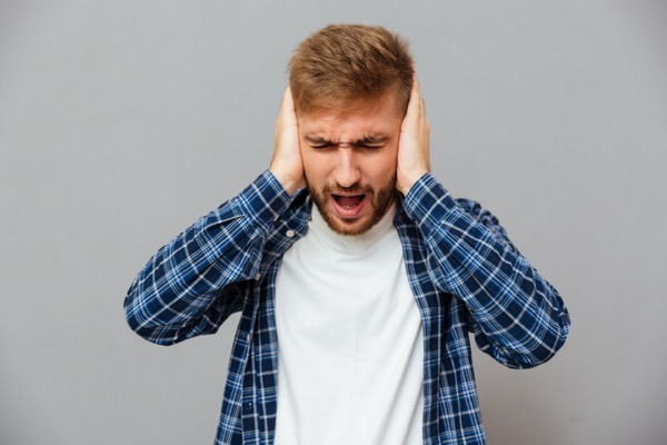 casual bearded man covering his ears and shouting isolated on a gray background Suz2N8Uhl