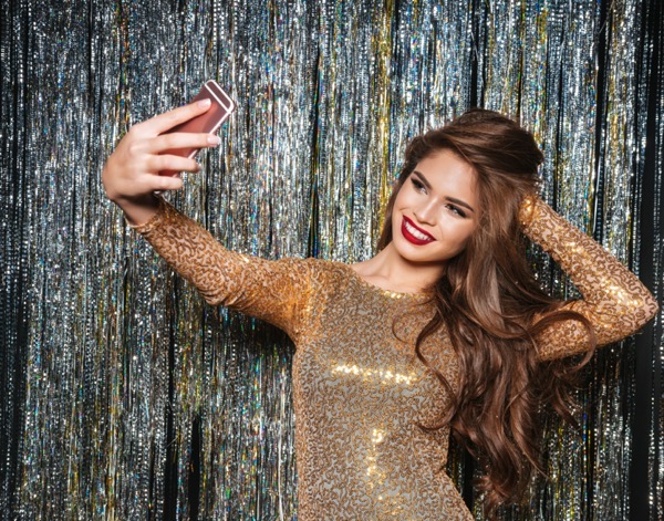 smiling attractive young woman in evening dress taking selfie with mobile phone over shining background SUGOPYXuhx