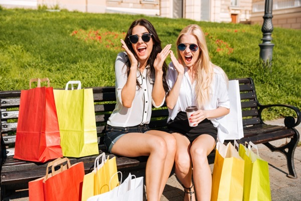 Graphicstock two young excited women having fun on bench after shopping together rdQDXiSng