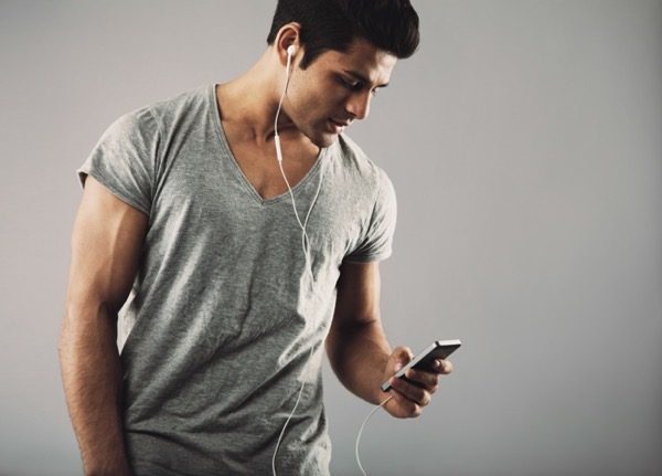 Portrait of casual young man with cell phone and headphones listening to music on grey background enjoying listening music on smartphone rpeAFPL4Kx
