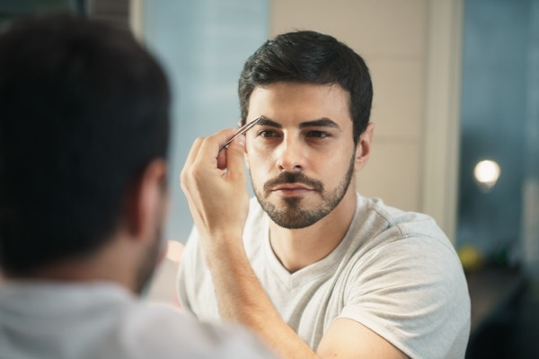 latino person with beard grooming in bathroom at home for morning routine and body care white metrosexual man trimming eyebrows with tweezers SIcgb9L 7